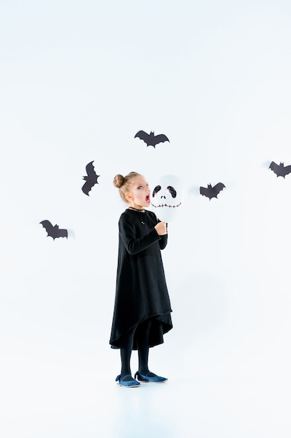 Hexe des kleinen mädchens im schwarzen langen kleid und in den magischen accessoires. halloween Kostenlose Fotos