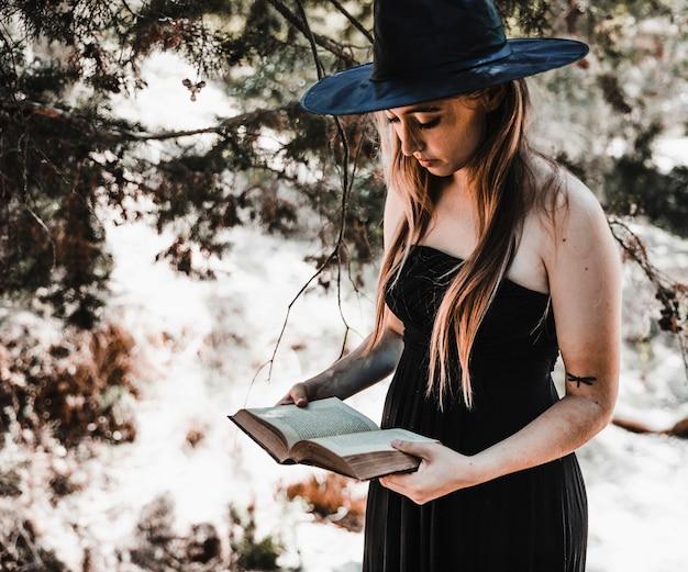 Hexe im hut, der gealtertes buch in der waldtageszeit liest Kostenlose Fotos