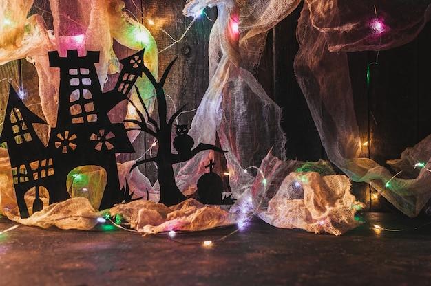 Hexenhaus mit einem grab und einem unheimlichen baum aus schwarzem papier auf einer holzwand mit einem spinnennetz. Premium Fotos