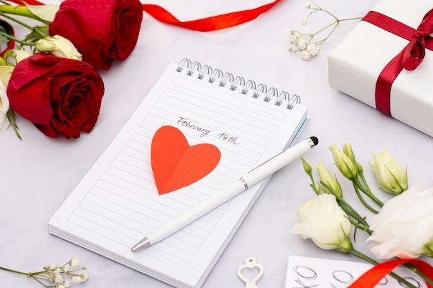 High angle arrangement mit notebook und rosen Kostenlose Fotos