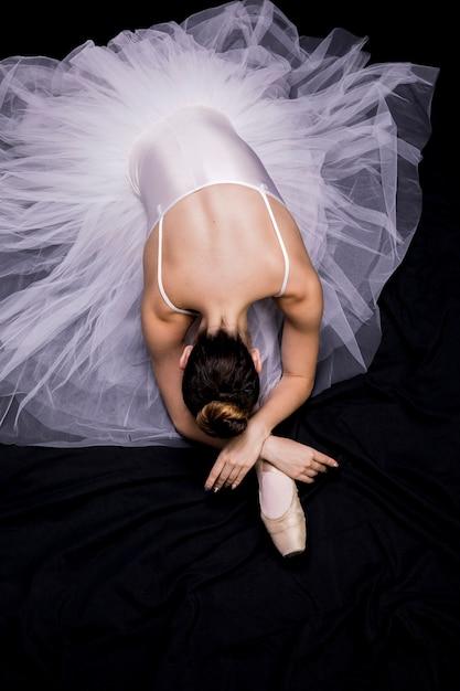 High angle ballerina sitzt auf ihrem bein Kostenlose Fotos