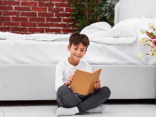 High angle boy auf dem boden lesen Kostenlose Fotos
