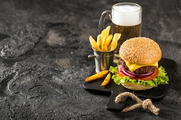 High angle burger auf schneidebrett mit pommes, sauce und bier mit kopierraum Premium Fotos