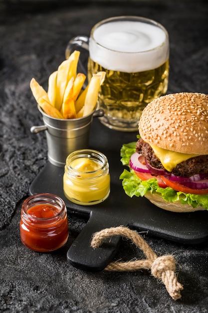 High angle burger auf schneidebrett mit pommes, sauce und bier Premium Fotos