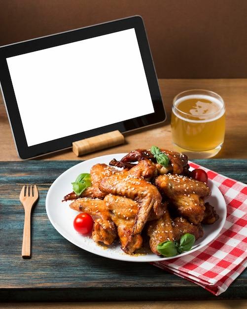 High angle chicken wings auf teller mit sesam Kostenlose Fotos
