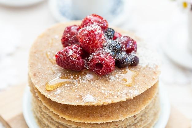 High angle closeup shot von rohen veganen pfannkuchen mit honig und beeren Kostenlose Fotos