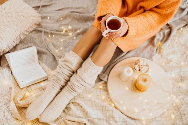 High angle frau genießt die winterferien mit einer tasse tee Kostenlose Fotos