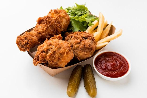 High angle fried chicken drumsticks mit ketchup und pommes Kostenlose Fotos
