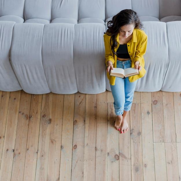 High angle girl reading in der nähe des sofas Kostenlose Fotos