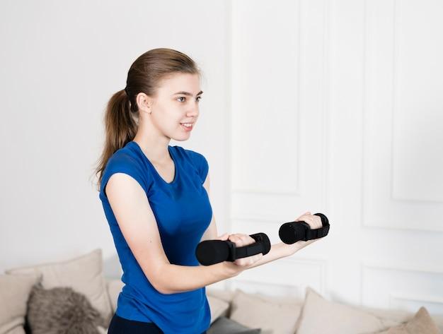 High angle girl training mit gewichten Kostenlose Fotos