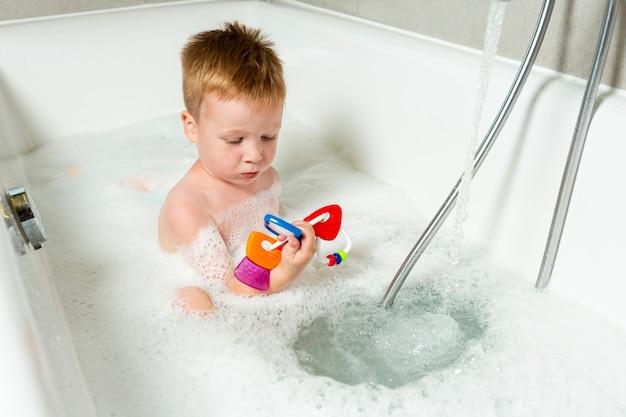 High angle kid in der badewanne mit spielzeug Kostenlose Fotos