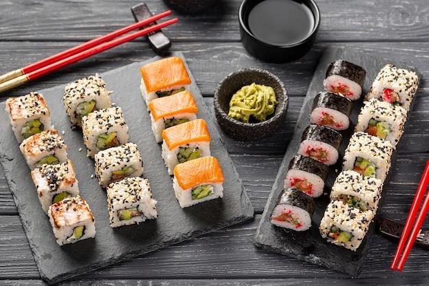 High angle maki sushi-sortiment auf schiefer mit stäbchen Kostenlose Fotos