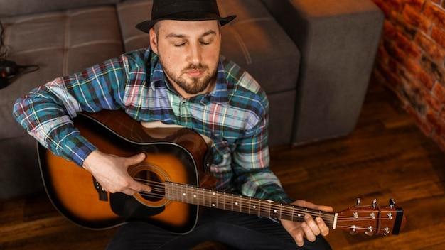 High angle mann spielt gitarre Kostenlose Fotos