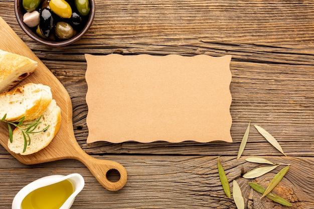 High angle oliven mischen brot und öl untertasse mit karton mock-up Kostenlose Fotos