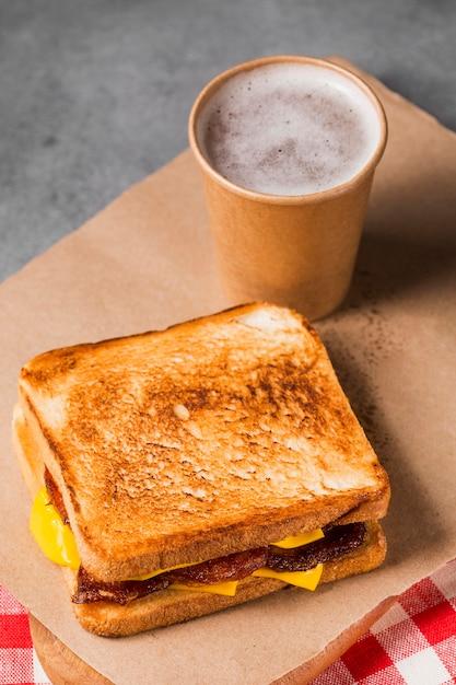 High angle sandwich mit speck und käse mit kaffee Kostenlose Fotos