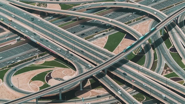 High angle shot einer großen autobahn mit mehreren straßen und einem zug, der durch die hauptstraße fährt Kostenlose Fotos