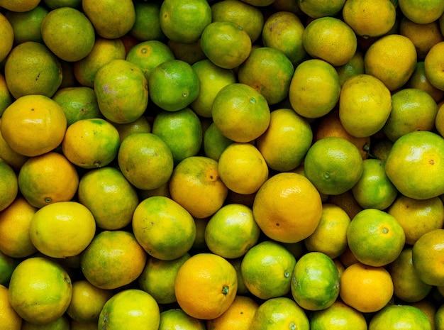 High angle shot einer köstlichen mandarine mit frischen früchten Kostenlose Fotos