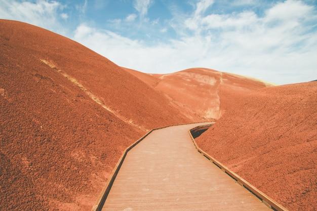 High angle shot einer künstlichen holzstraße in den roten sandhügeln unter dem hellen himmel Kostenlose Fotos