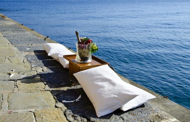 High angle shot einer obstschale und einer flasche champagner auf dem pier am ruhigen ozean Kostenlose Fotos