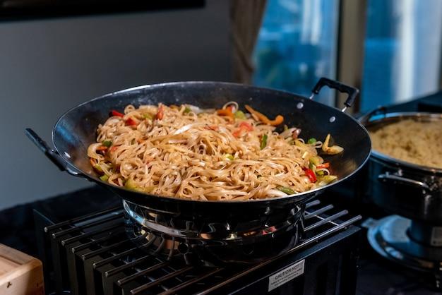 High angle shot einer pfanne mit köstlichen nudeln und gemüse in einer küche gefüllt Kostenlose Fotos