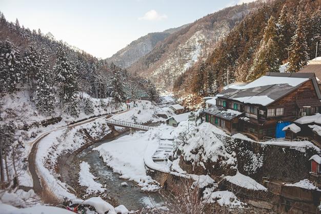 High angle shot eines holzhauses, umgeben von bewaldeten bergen, die im winter mit schnee bedeckt sind Kostenlose Fotos