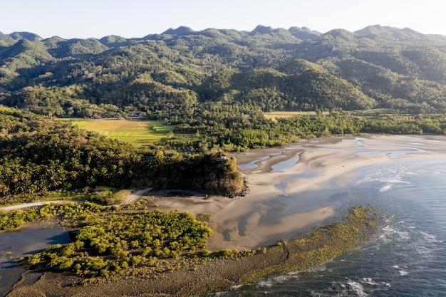 High angle shot eines meeres in der nähe eines ufers und berge, die tagsüber mit bäumen bedeckt sind Kostenlose Fotos