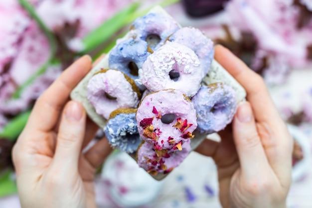 High angle shot von den händen einer person, die einige lila und blaue vegane donuts über einem tisch halten Kostenlose Fotos