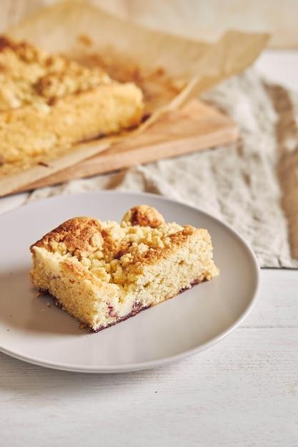 High angle shot von einem stück köstlichen jerry crumble sheet cake auf einem weißen holztisch Kostenlose Fotos