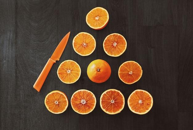 High angle shot von geschnittenen orangen in dreiecksform neben einem orangefarbenen messer auf einer schwarzen oberfläche Kostenlose Fotos