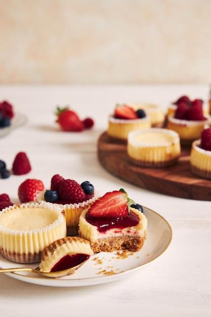 High angle shot von käse cupcakes mit fruchtgelee und früchten auf einem holzteller Kostenlose Fotos