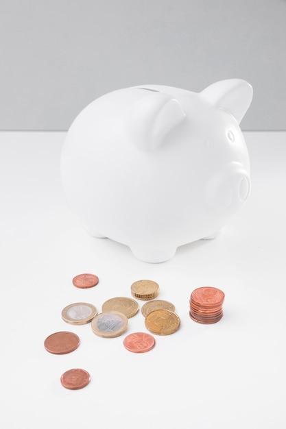 High angle sparschwein mit münzen daneben Kostenlose Fotos