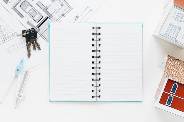 High angle view blueprint; schlüssel; tagebuch mit hausmodell öffnen Kostenlose Fotos