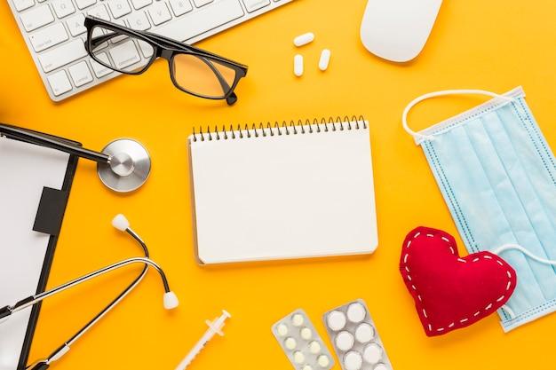 High angle view stethoskop; injektion; medizin in blisterpackungen; maske; spiralblock; genähte herzform vor gelbem hintergrund Kostenlose Fotos