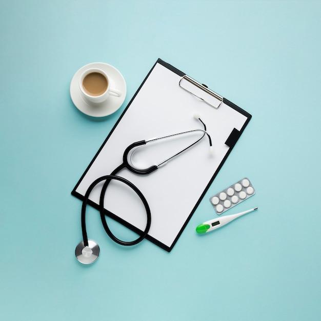 High angle view zwischenablage mit papier und kaffeetasse; thermometer; stethoskop; blister verpackte medizin gegen blauen hintergrund Kostenlose Fotos