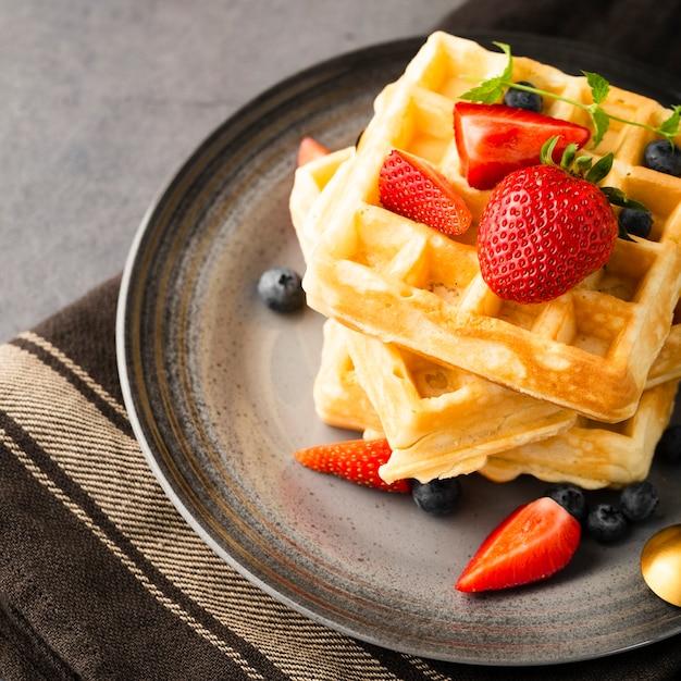 High angle waffles mit erdbeeren und cranberries Kostenlose Fotos