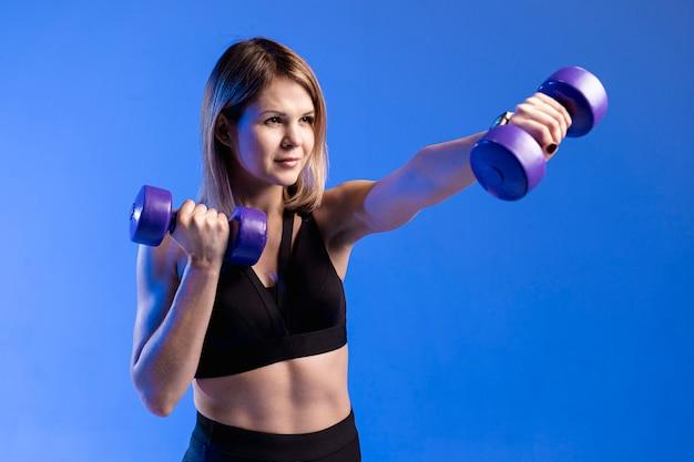 High angle woman training mit gewichten Kostenlose Fotos