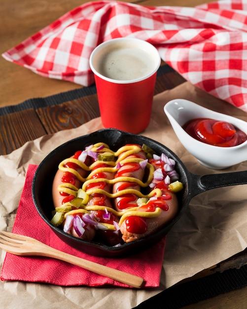 High angle würstchen in pfanne mit saucen Kostenlose Fotos