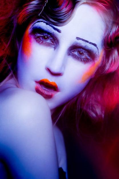 High fashion model frau in bunten hellen lichtern, die im studio aufwerfen Premium Fotos