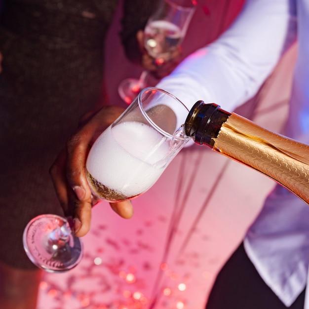 High view männchen, das champagner in ein glas gießt Kostenlose Fotos
