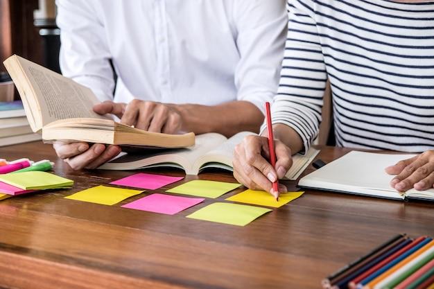 Highschool- oder student-gruppe, die am schreibtisch in der studierenden und lesenden bibliothek sitzt, hausaufgaben macht und lektion üben Premium Fotos