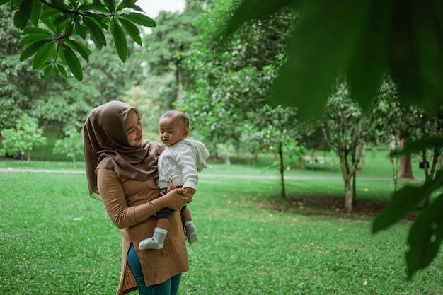 Hijab frau hält kleines baby Premium Fotos