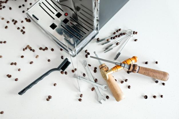 Hilfsmittel für die reparatur der kaffeemaschinennahaufnahme. kaffeebohnen, holzbrett, kaffeemaschine, küchentisch Premium Fotos