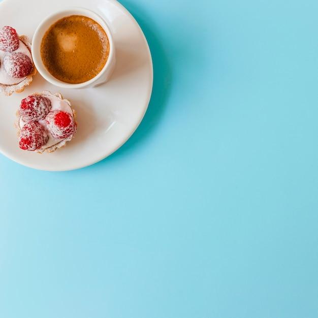 Himbeertörtchen mit sahne und kaffeetasse auf platte über dem blauen hintergrund Kostenlose Fotos