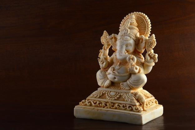 Hindu-gott ganesha. ganesha idol auf braunem hintergrund Premium Fotos