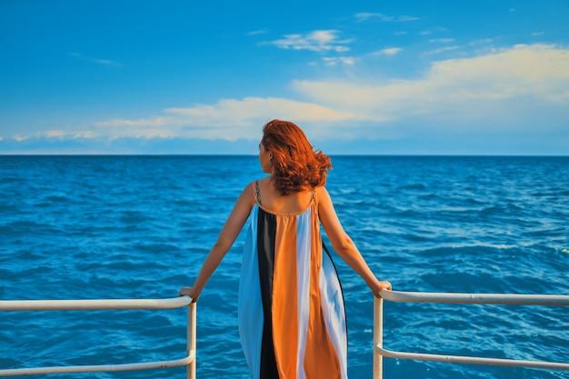 Hinter dem mädchen am pier. frau im colorfull kleid, das auf dem pier steht. Premium Fotos