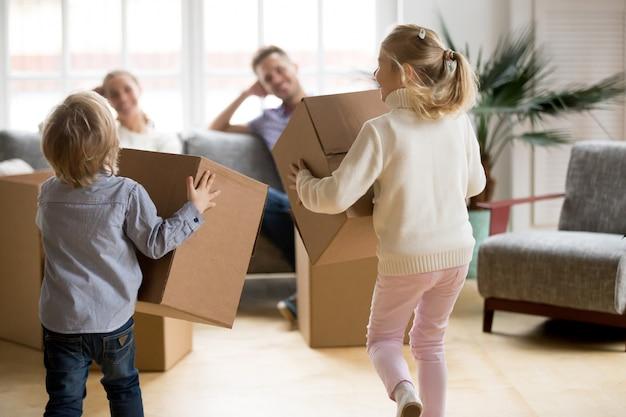 Hintere ansicht an den kindern, die mit kästen am beweglichen tag spielen Kostenlose Fotos