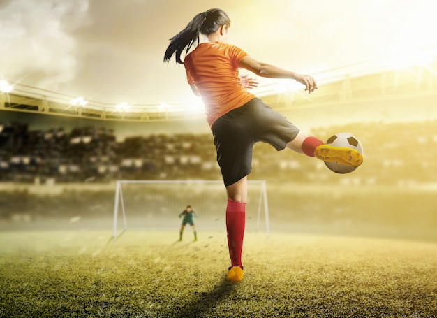 Hintere ansicht der asiatischen fußballspielerfrau im orange trikot den ball im strafraum tretend Premium Fotos