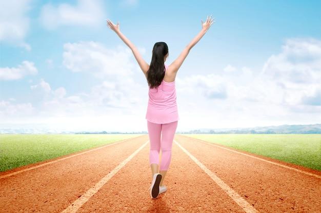Hintere ansicht der asiatischen läuferfrau mit aufgeregtem ausdruck nach einem lauf auf der laufbahn Premium Fotos