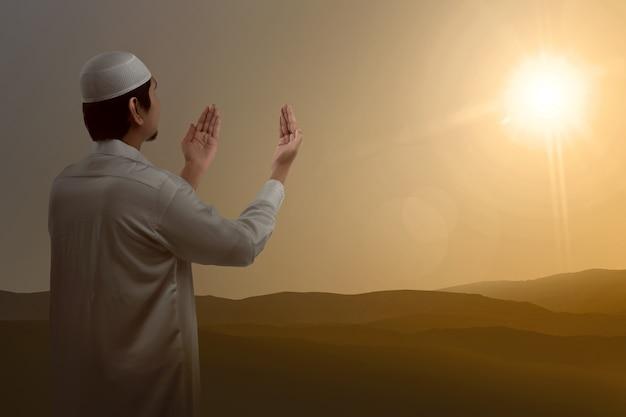 Hintere ansicht der asiatischen moslems hand anhebend und betend Premium Fotos