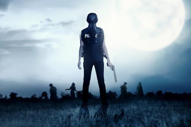 Hintere ansicht der asiatischen polizeibeamtin mit dem gewehr auf ihrer hand stellen die zombies auf der rasenfläche gegenüber Premium Fotos